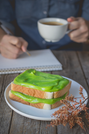 break time, coffee time with pandan custard cream on toasted, holding coffee cup and working, for advertising or busy work concept