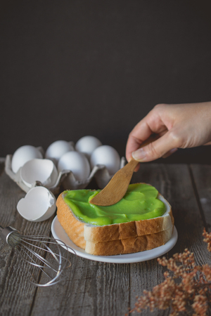 hand applying  pandan custard cream on to toasted, easy breakfast in morning with bread and custard cream topping