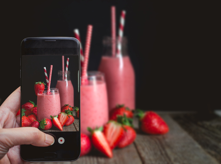 Taking a photo by Finger Pressing on Smartphone for Photograph Strawberry Smoothie with wood and Copy Space in Relax Concept, Image for Beverage Advertise or Social Media with Drink Concept