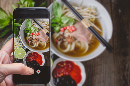 vietnamse: Taking a photo by Finger Pressing on Smartphone for Photograph Pho Vietnamse Noodle Soup on Wooden Background with Copy Space. Image for Food Advertise Concept