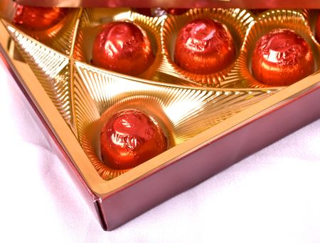 chocolates wrapped in red foil, in a box Stock Photo