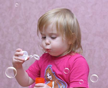A little girl blows bubbles Stock Photo