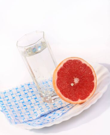 Juicy red grapefruit and a glass of mineral water on a white background. Stock Photo