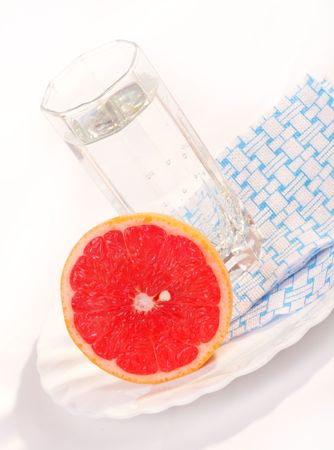 Juicy red grapefruit and a glass of mineral water on a white plate