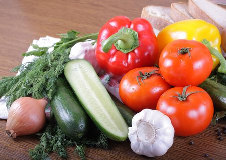 Fresh vegetables, tomatoes, cucumbers, garlic and others on a wooden table
