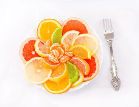 dessert of citrus and marmalade on a white background (isolated) with a fork