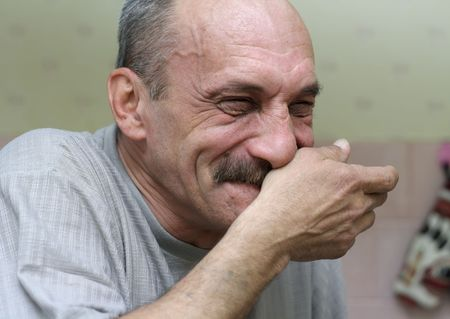 old bald man laughs and covers her mouth with his hand