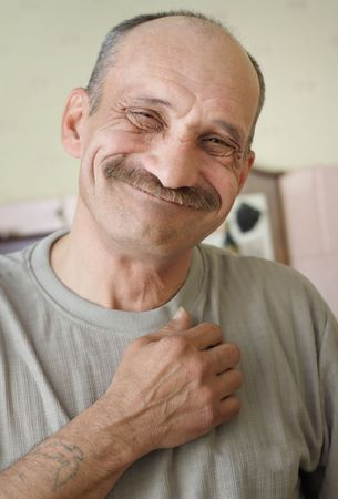 old bald senior with a mustache standing and smiling photo