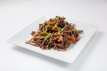 Soba Buckwheat noodles with chicken teriyaki on a white background