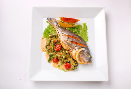dorado fish baked with greens and green beans on a white background