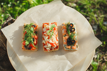 Italian tomato and cheese bruschetta. Tapas, antipasti with chopped vegetables, herbs and oil on grilled ciabatta and baguette bread. Stock Photo