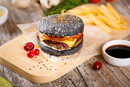 Close up Modern black Burger with beef meat, bacon, cheese, lettuce and vegetables garnished with fried potato wedges and barbecue sauce on the wooden stand