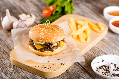Juicy burgers with ingredients: salad, mushrooms, onion, beef, pepper and tomato sauce over wooden table. Black background and copy space. Stock Photo