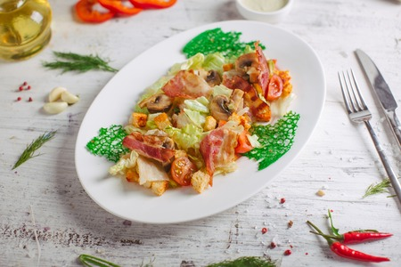 salad preparation - adding croutons in a warm salad of chicken breast, quail eggs and herbs and fried mushrooms Stock Photo