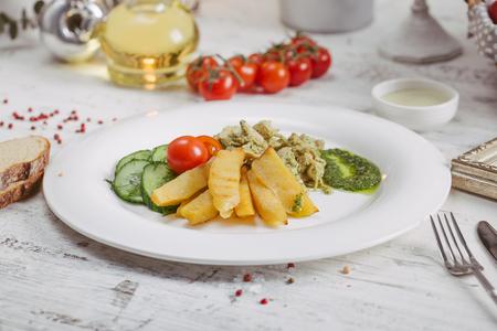 Salad.Chorizo sausage, lettuce, pickled cucumber fried potato with mayonnaise.Dark background Stock Photo