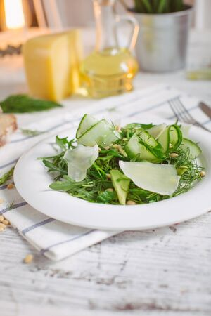 At the center of the frame white plate with a salad of arugula, rocket, avocado, pomegranate seeds, parmesan cheese, spices. Rocket salad on a white background. Horizontal shot. Top view. Stock Photo