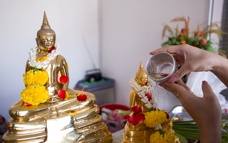 Songkran day. Thai culture concept. Hand woman use the sliver bow to golden buddha statue Stock Photo