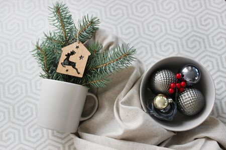 light cup and plate with christmas balls on a light table, closeup. Foto de archivo