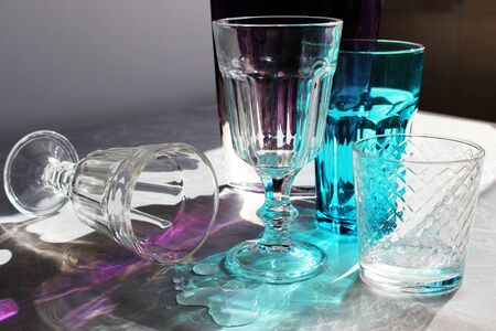 multi-colored glasses on a table in the rays of sunlight