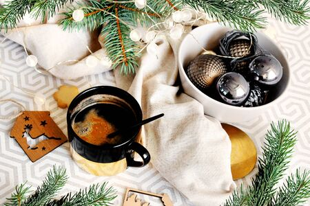 Christmas background with place for text. Christmas balls and fir branches with a golden cup of coffee. view from above. Archivio Fotografico