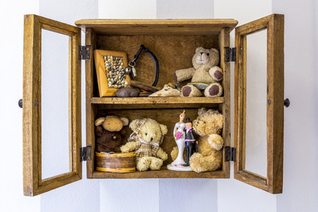 Old rustic wood wall mounted display cabinet, items, toys and memories.