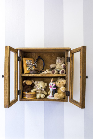 old items: Old rustic wood wall mounted display cabinet, items, toys and memories. Vertical position. Stock Photo