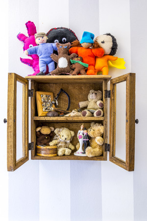 old items: Old rustic wood wall mounted display cabinet, items, stuffed toys and memories.