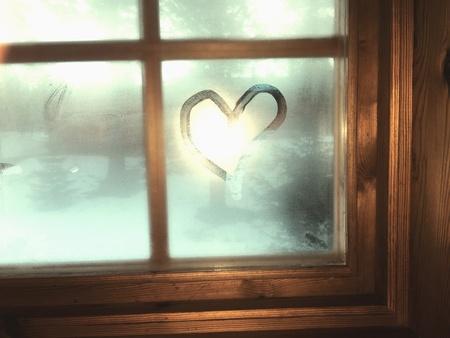 Heart on moisture window winter cabin.