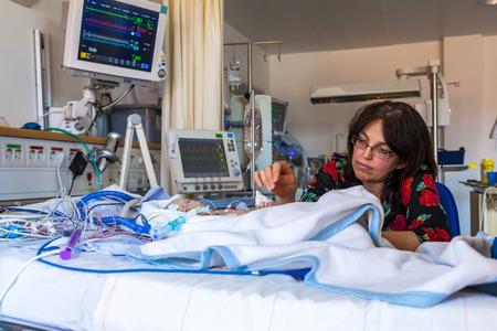Madre con el bebé enfermo, niño, unidad de cuidados intensivos.