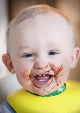 messy: Cute baby with messy face eating dessert.