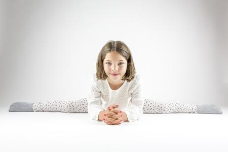 leaning forward: Girl sits in splits on floor leaning forward.