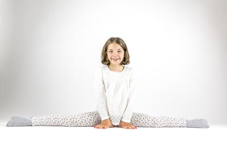 splits: Girl sits in splits on floor.
