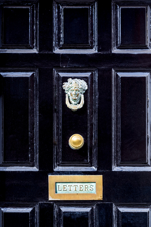 scraped: Close up of black wooden entrance door with brass letterbox in traditional style, Dublin Ireland. Stock Photo