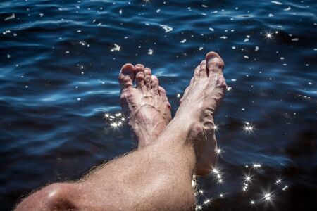 Summer feet against glimmering water.
