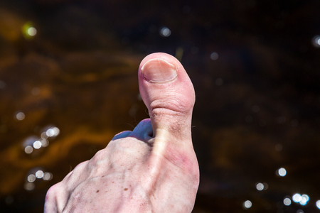 big toe: Close up of big toe against shimmering water.