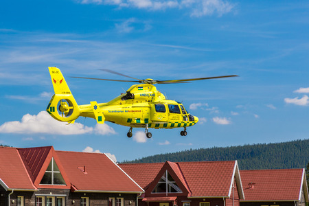Ambulance helicopter close to houses. Klövsjö, Jämtland, Sweden - July 25, 2016: Ambulance helicopter close to houses after take off. Ambulance helicopter after take off close to houses.
