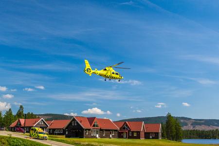 helicopter rescue: Ambulance vehicle and ambulance helicopter. Klövsjö, Jämtland, Sweden - July 25, 2016: Ambulance vehicle and ambulance helicopter rescue. Ambulance vehicle and helicopter after emergency rescue. Editorial