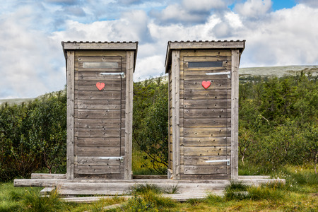 outhouse: Two wooden outhouse toilets with red heart in mountain landscape.