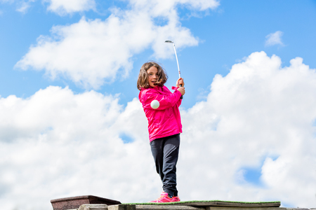 Young cute girl playing golf, low angle view with clouds in background.