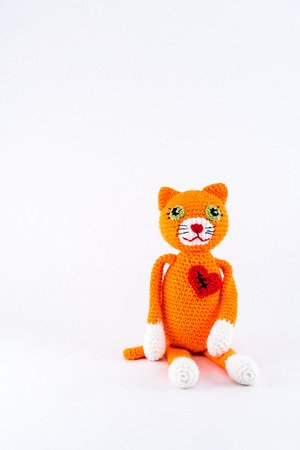 Broken heart with scar, stuffed toy cat. Isolated on white.