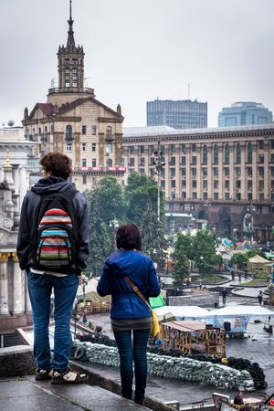 Tourists looking out over barricades on  Maidan Nezalezhnosti. Tourist view over  Maidan Nezalezhnosti., Kiev Ukraine.   Maidan Nezalezhnosti, Kiev, Ukraine - May 15, 2014: View over the square. Editorial