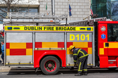 Firefighter in front of a fire engine.  Dublin city, Ireland - April 21, 2016: Irish firefighter from Dublin fire brigade in front of fire engine.  Irish firefighter and fire engine.
