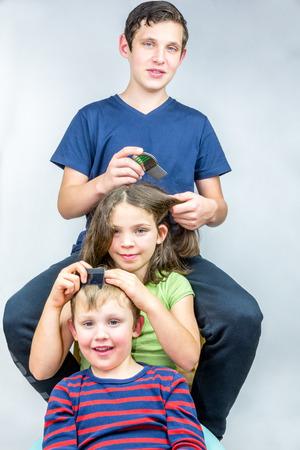 helpfulness: Three children who comb each others head. Efficient head lice treatment, studio portrait shot.