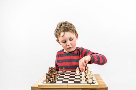 landscape format: Boy playing chess with himself, portrait studio shot. Landscape format.