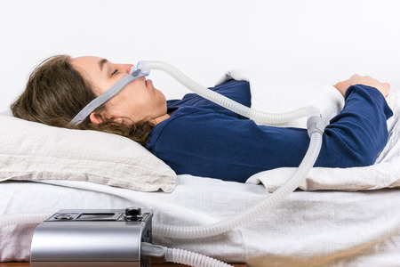 snore: Woman sleeping on her back with CPAP machine in the foreground, sleep apnea treatment. Profile shot. Stock Photo