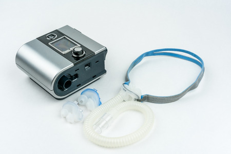 CPAP machine with hose and mask for nose. Treatment for people with sleep apnea, respiratory, or breathing disorder. Stock Photo