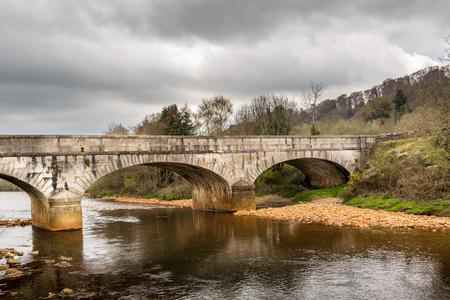 irish landscape: Old ancient stone bridge over calm river, beautiful Irish landscape. Scenic view. Stock Photo