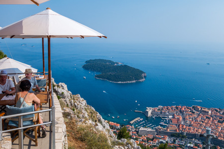 above 18: People in a restaurant above Dubrovnik.  Dubrovnik, Croatia - July 18, 2015: Two men and one woman in a restaurant on top of the mountain above Dubrovnik.  Summer view of Dubrovnik.