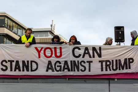 urging: People put up anti Donald Trump banner. Stockholm, Sweden - January 21, 2017: Anti Donald Trump banner and people at demonstration in Stockholm January 21, 2017. People behind anti Donald Trump banner
