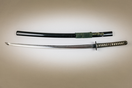 Japanese sword isolated on white. Iaido training sword iaito. Studio shot white light in center.